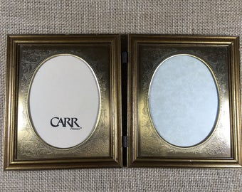 vintage gold colored dual portrait frames.hinged. carr frames. with glass.