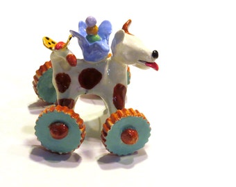 CeramicDog on Wheels With a Birds Nest and a Butterfly Toy