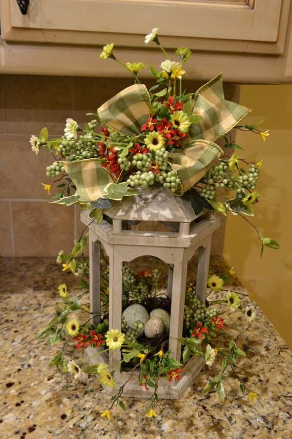 Cream wooden lantern with flowers and nest