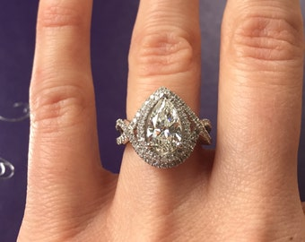 2.11 carat (1.63 carat center) H SI3 certified pear shaped diamond engagement ring. Offering flexible layaway.