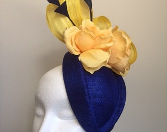 Blue and yellow fascinator with silk abaca loops,feathers and flowers.