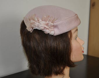 Elegant evening wear hat. Pink fabric accented with feathers like fabric accents.