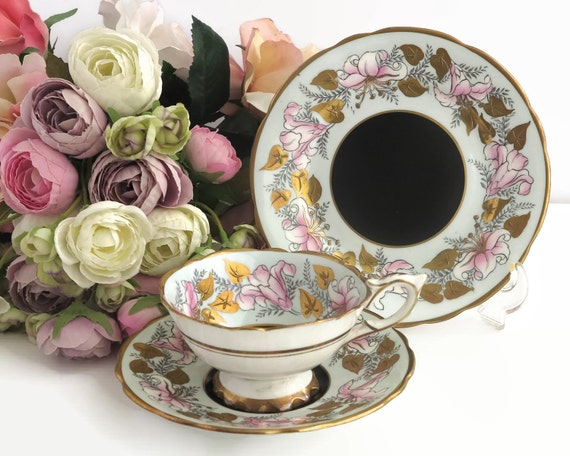 Royal Stafford cup, saucer, plate, Morning Glory pattern of pink flowers with gilt and black accents, footed cup, 1950s