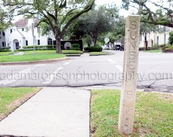 Photograph of SUNSET Blvd cement street sign in the West University area of Houston, Texas