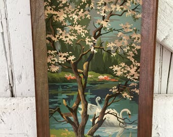 Vintage paint by number painting in frame with swans in lake with cherry blossoms