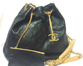 Vintage CHANEL black and beige calf leather hobo bucket shoulder bag with charm.