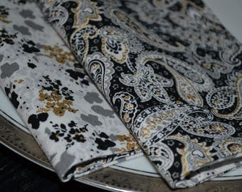 Set of 8 reversible cloth napkins featuring fblack, white, and gold paisley and flowers.
