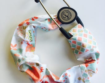 Stethoscope cover featuring a peach teal and gold floral pattern