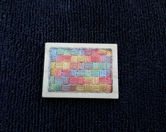 Brooch, hand stitched in vibrant pinks, blues, yellows, mauve & green in a basketweave design, set in a natural wooden frame. Totally unique
