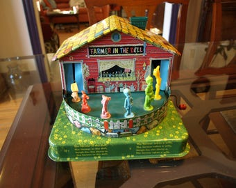 A Mattel  Music  Maker Toy Stock 503 - Farmer in the Dell Tin Toy Crank Music Box – 1953