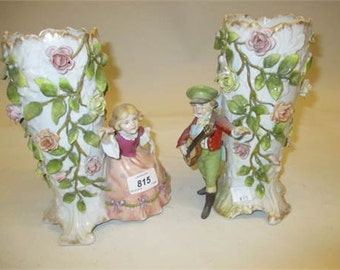 Pair of Continental porcelain figural vases with applied floral decoration, german