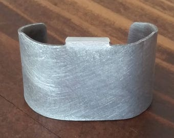 Brushed aluminum Tail Cuff slides onto most any pony tail holder in 7 seconds. Cover that tail! Carry it with you. It's easy to put on.