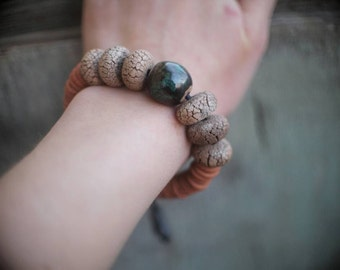 Ceramic bracelet with central  glazed bead and handmodeled side craquelure bisque beads