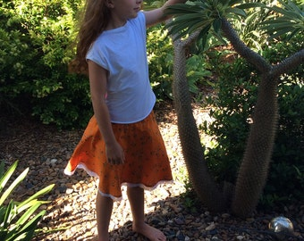 Girls, tweens summer, spring skirt in orange floral cotton print with yoke and lace trim.