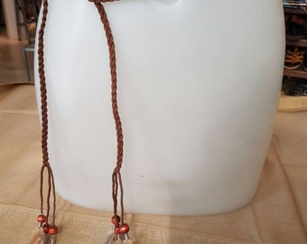Strap of leather braided with feathers