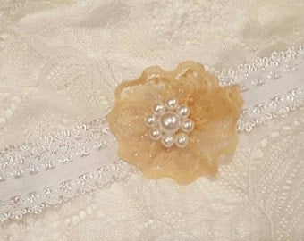 Beige lace flower with pearl center.