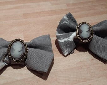 Pair Of Clip on Vintage Style Hair-Bows With Cameo Embellishment And Black Floral Fabric.