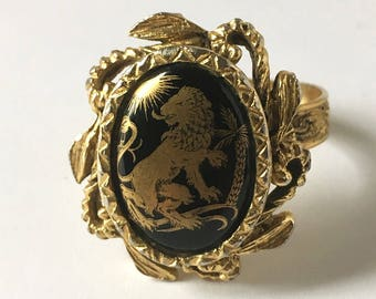 Vintage Gold Tone Ring with Adjustable Band and Gold Heraldic Lion Design on Black Background