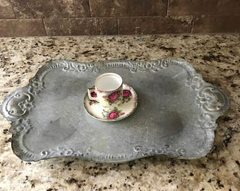 Vintage silver serving tray with teacup and saucer.