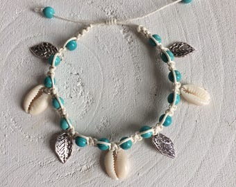 Knotted bracelet with turquoise/blue beads, cowry shells and silver charms
