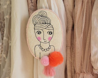 Needle-drawn girl face brooch with pom-poms