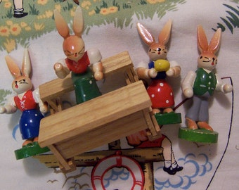 four tiny wooden rabbits figurines