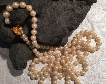Hand knotted pearl strand necklace .