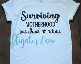 Surviving Motherhood One Drink at a Time Graphic T Shirt Mommyhood Funny Shirts Moms that Drink
