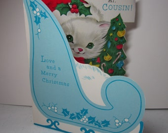 Colorful unused 1950's-60's Norcross die cut red flocked juvenile christmas card to cousin,fluffy white kitten in blue sleigh holds tree