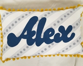 Baby pillow in light gray stripes and navy blue lettering. Personalized with name.
