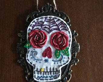 Embroidered sugar skull wall plaque.