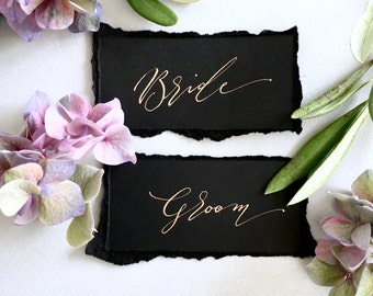 Torn black wedding place name tags with gold handwritten calligraphy