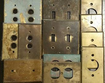 Twelve various vintage brass metal switch plates.