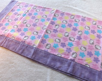 newborn baby receiving blanket made from pink Hello Kitty Flower Power with purple backing, dog blanket, lap blanket, self binding