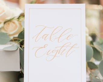 White and gold table numbers