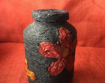 Hemp Stash Jar with Red, Green, and Orange Flowers.