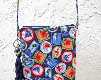 Travel sticker crossbody bag. Blue purse with sailboat, flamingo and palm tree print. Tassel keychain purse charm. Fun vacation pouch.