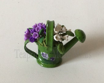 Miniature watering can with lilac flowers