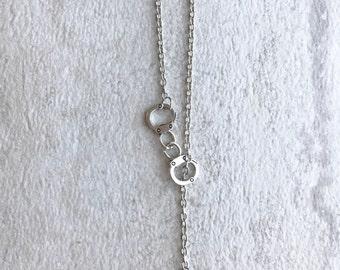 Silver gun and handcuffs necklace
