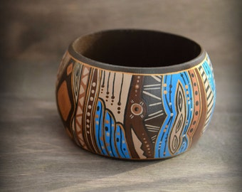Wooden bracelet with a painted abstract design. Detailed painting. Brown background.