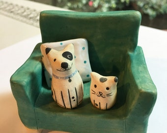 Cute Dog and Cat Friends Sitting on a Blue/Green Chair Ceramic Sculpture