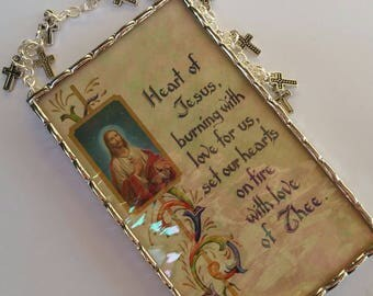 Sacred Heart of Jesus plaque soldered in iridescent water glass with tiny silver tone crosses in the hanger and swag