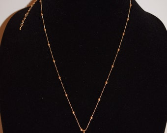Gold ball necklace with crystal pendant