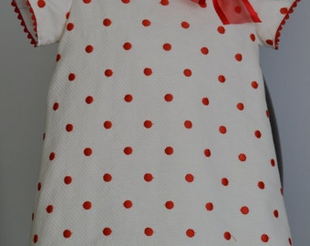 Beige girl dress honey pique with red Polka dots, lined in batiste with Organza ribbon and three buttons in the back. Handmade. Bebesitos.
