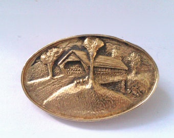 gold coloured scenic brooch