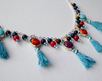 Pendant silver necklace with colourful gemstones and silver charms, and a cluster of beads