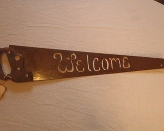 Welcome sign cut on an old hand saw.  Plain and simple, yet with enough quirk to make people take notice.