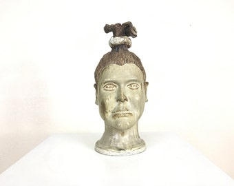Two faced ceramic head sculpture