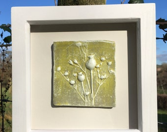Framed original wall art, clay impression of dried flower seed heads yellow and white in a white wooden frame.