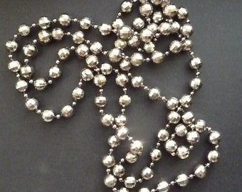 Long single strand vintage beaded necklace, silver shiny plastic multifaceted beads